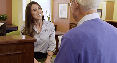 Screenshot from Malaga Bank's commercial featuring a teller speaking to an older gentleman.