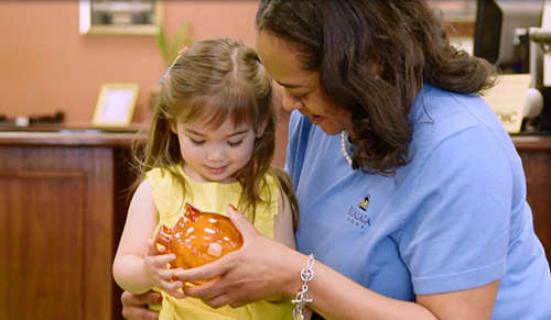 Screenshot from Malaga Bank's commercial featuring Kim Edwards with a young customer.