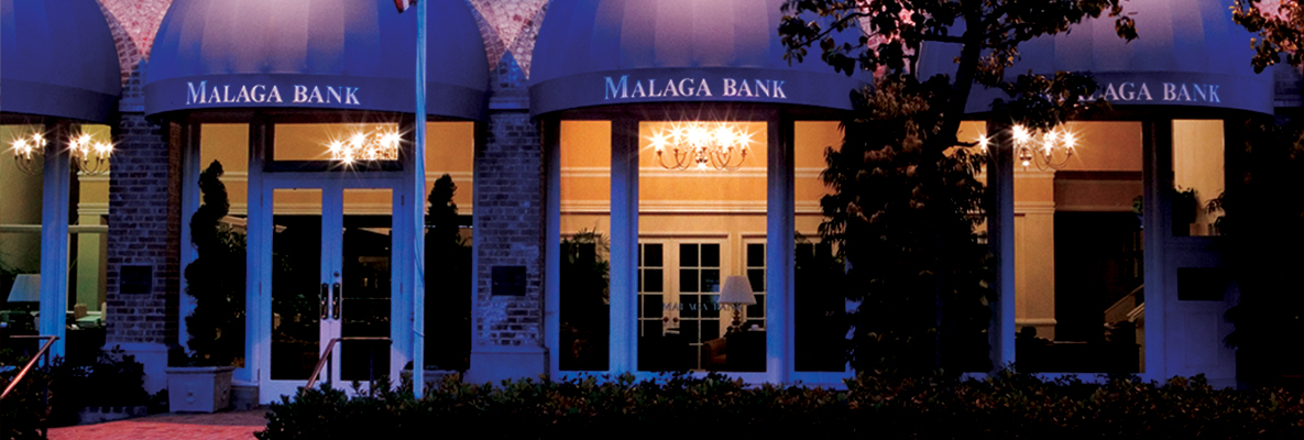 Image of Malaga Bank's building illuminated at night.